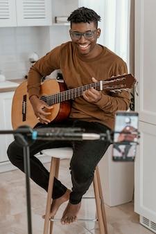 집에서 기타를 연주하고 스마트 폰으로 녹음하는 웃는 남성 음악가의 전면보기