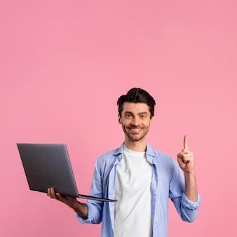 Вид спереди смайлика человека, держащего ноутбук и указывающего вверх
