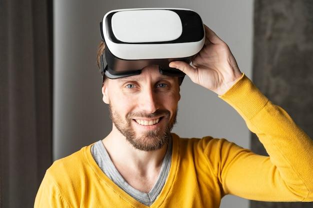 Вид спереди смайлика человека, позирующего с гарнитурой виртуальной реальности