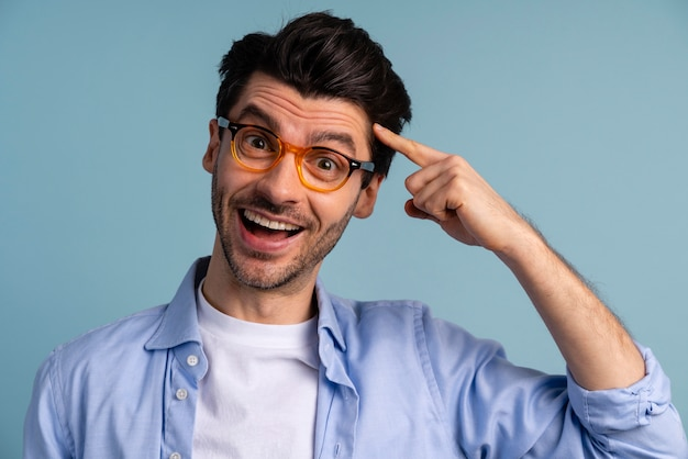 그의 머리에서 가리키는 안경 웃는 남자의 전면보기