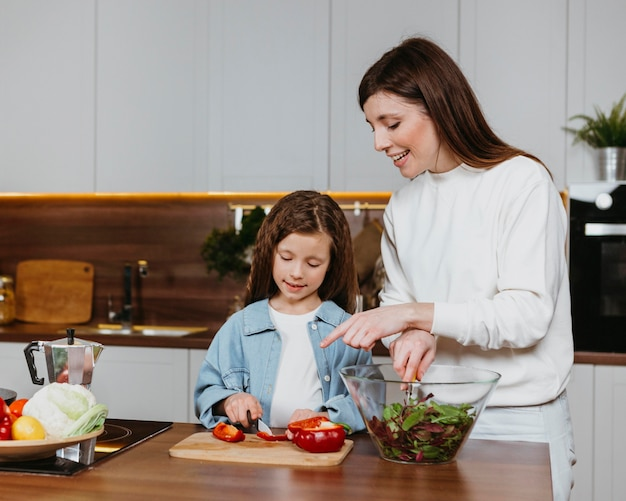 キッチンで食事を準備する笑顔の母と娘の正面図