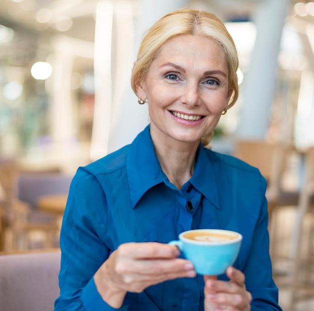 仕事をしながら一杯のコーヒーを楽しむ笑顔の古いビジネス女性の正面図