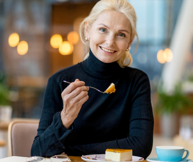 Вид спереди смайлика пожилой деловой женщины, имеющей десерт во время работы