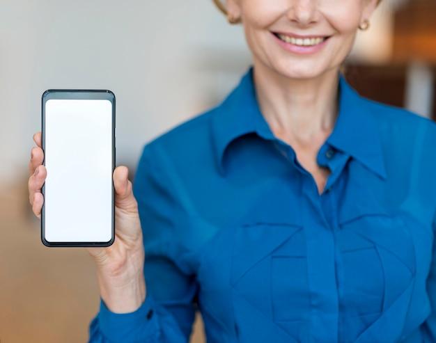 Вид спереди смайлика пожилой деловой женщины, держащей смартфон