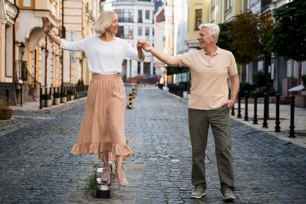 屋外散歩を楽しむ笑顔の年配のカップルの正面図