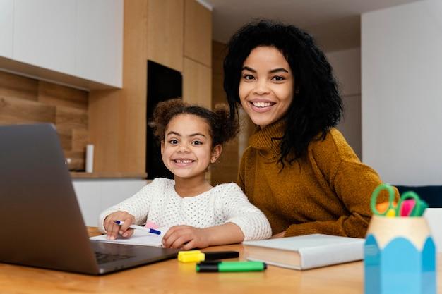 Улыбающаяся девочка-подросток, помогающая младшей сестре во время онлайн-школы с планшетом, вид спереди
