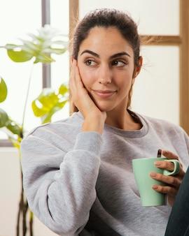 Вид спереди смайлика женщины с кофе дома
