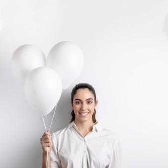 Вид спереди смайлик женщина держит воздушные шары