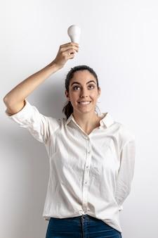 Вид спереди смайлик женщина держит лампочку