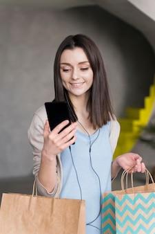 Вид спереди смайлик женщина, держащая смартфон и бумажные мешки