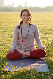 屋外でヨガマットで瞑想するスマイリー女性の正面図