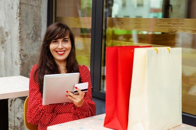태블릿 및 신용 카드를 사용하여 판매 품목을 주문하는 웃는 여자의 전면보기