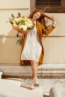 봄 꽃의 부케와 함께 야외에서 웃는 여자의 전면보기