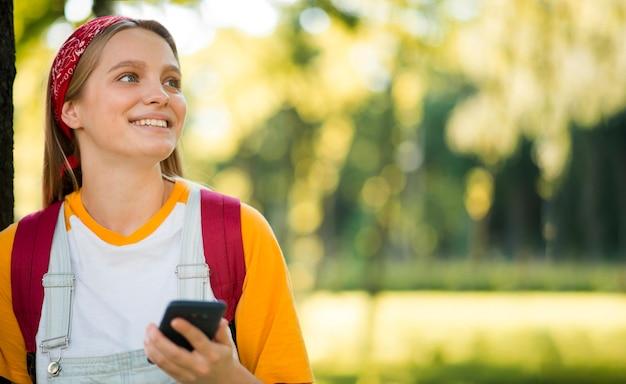 スマートフォンで屋外のスマイリー女性の正面図