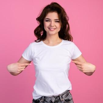 自分を指している笑顔の女性の正面図