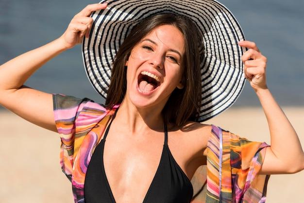 ビーチでポーズをとって笑顔の女性の正面図
