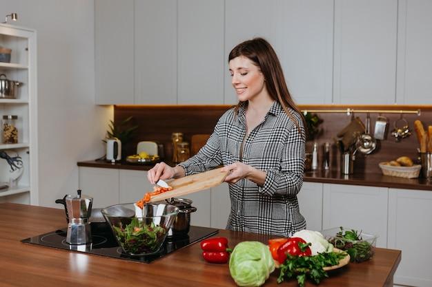 집에서 부엌에서 음식을 준비하는 웃는 여자의 전면보기
