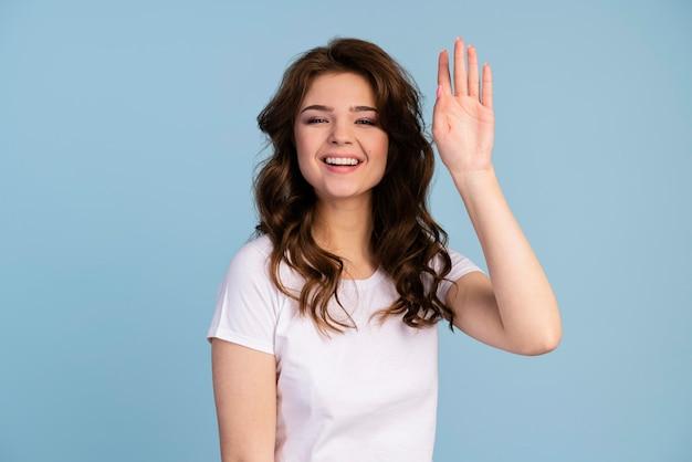 手を振っている笑顔の女性の正面図