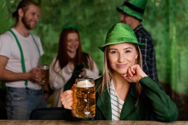 聖を祝う帽子をかぶったスマイリー女性の正面図。飲み物と友達とのパトリックの日