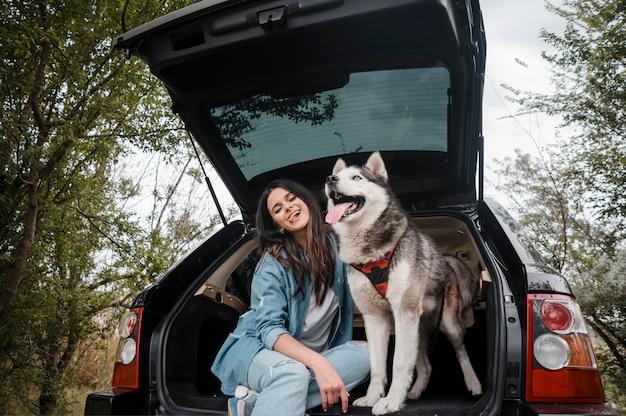 Вид спереди смайлика с ее милой хаски, путешествующей на машине