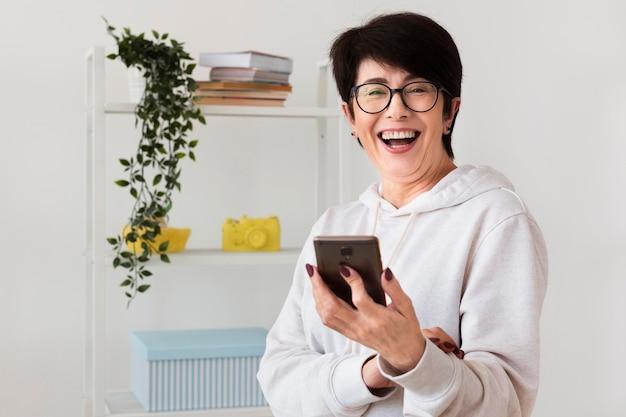 スマートフォンで笑顔の女性の正面図