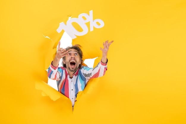 黄色い紙の引き裂かれた穴で10パーセントの数字で遊んでいる笑顔のひげを生やした男の正面図