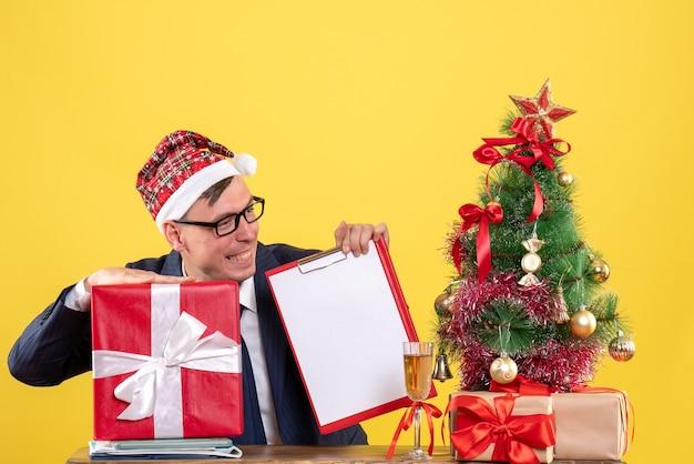 Вид спереди улыбающегося делового человека, сидящего за столом возле елки и подарков на желтом