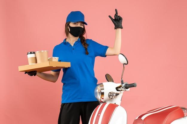 パステル ピーチ色の背景にコーヒーの小さなケーキを保持しているオートバイの隣に立っている医療マスク手袋を着た笑顔の宅配便の女の子の正面図