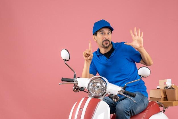 スクーターに座って、パステル カラーの桃の背景に 5 つを示す上向きの帽子をかぶった笑顔の宅配業者の男の正面図
