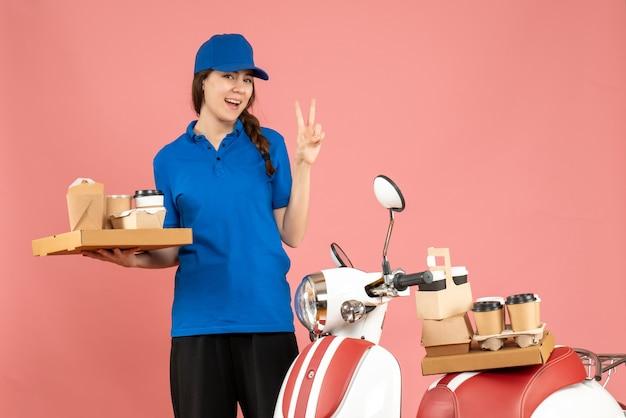 Вид спереди улыбающейся курьерской дамы, стоящей рядом с мотоциклом, держащей кофе и маленькие пирожные, делая жест победы на фоне пастельного персикового цвета