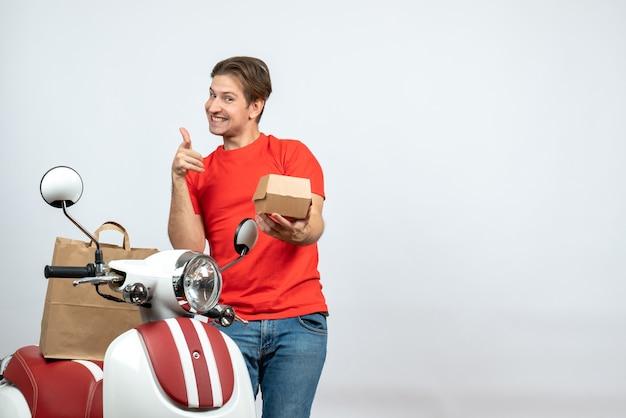 白い背景の上のokジェスチャーを作る注文を与えるスクーターの近くに立っている赤い制服を着た笑顔の配達人の正面図