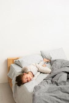Вид спереди улыбающейся девушки в постели с копией пространства
