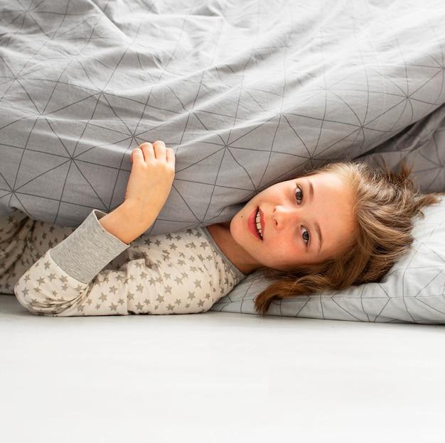 ベッドで微笑んでいる女の子の正面図