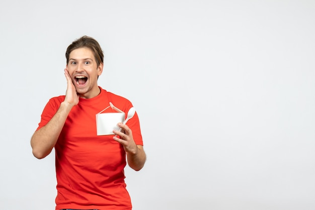 白い背景の上の紙箱とスプーンを保持している赤いブラウスの笑顔の幸せな若い男の正面図