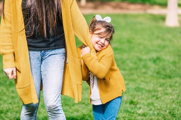 公園で立っているとカメラを見て頭のネクタイと笑顔の少女の正面図