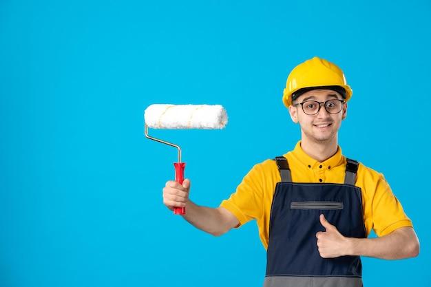 Вид спереди улыбающегося мужчины-строителя в униформе и шлеме с малярным валиком на синем