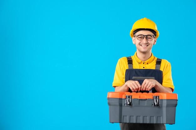 青の彼の手でツールボックスと制服を着て笑顔の男性ビルダーの正面図