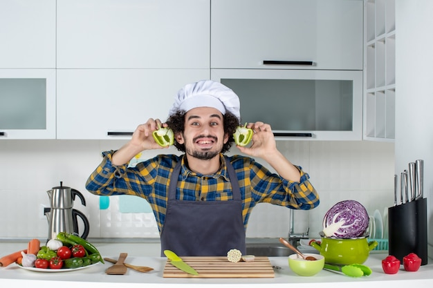 Вид спереди улыбающегося шеф-повара со свежими овощами, готовящего с кухонными принадлежностями и держащего зеленый перец на белой кухне