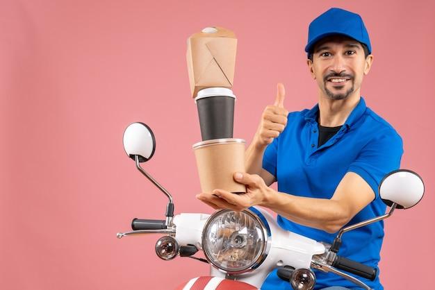 확인 제스처를 만드는 주문을 보여주는 스쿠터에 앉아 모자를 쓰고 웃는 남성 배달 사람의 전면보기