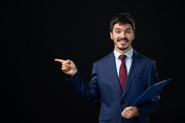 문서를 들고 고립 된 어두운 벽에 오른쪽에 뭔가를 가리키는 소송에서 웃는 남성 회사원의 전면보기