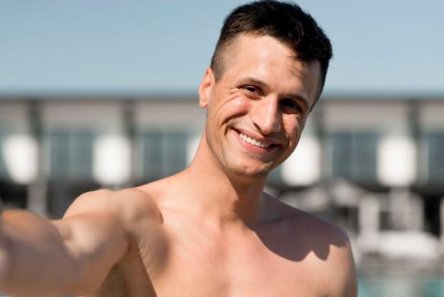 Вид спереди улыбающегося человека, принимая селфи