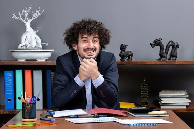 オフィスの机に座っている笑顔のサラリーマンの正面図