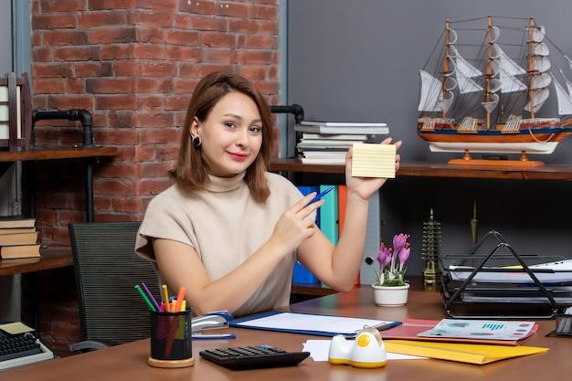 オフィスで働くメモ用紙を保持している笑顔の女性の正面図