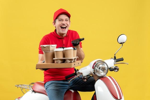 注文を保持しているスクーターに座って注文を配信医療マスクで赤いブラウスと帽子の手袋を身に着けている不思議な宅配便の男の笑顔の正面