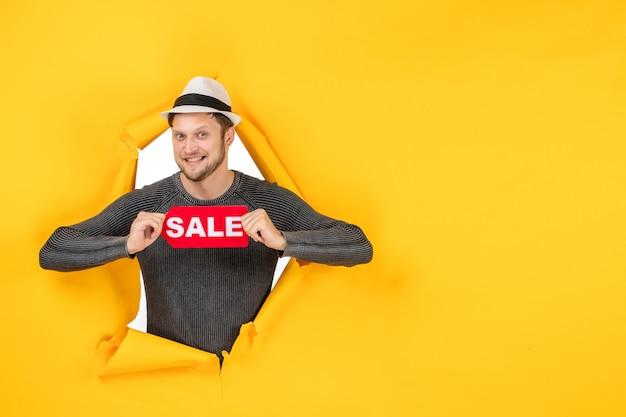 노란색 벽에 찢어진 판매 기호를 보여주는 웃는 젊은 성인의 전면보기