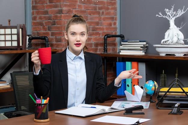 테이블에 앉아 사무실에서 빨간 컵을 들고 웃는 젊은 여성의 전면 보기
