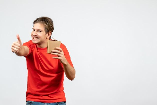白い背景でokジェスチャーを作る小さなボックスを保持している赤いブラウスで笑顔の若い男の正面