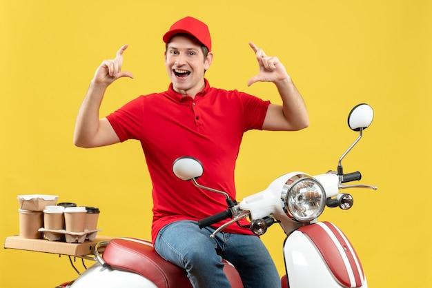 黄色の背景に正確な何かを作る注文を配信する赤いブラウスと帽子を身に着けている笑顔の若い男の正面図