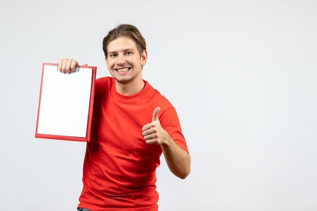 白い背景でokジェスチャーを作るドキュメントを保持している赤いブラウスで笑顔の若い男の正面図