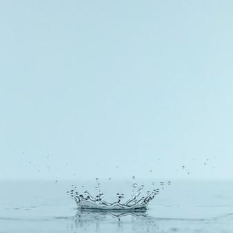 コピースペース付きのドロップからの水のしぶきの正面図